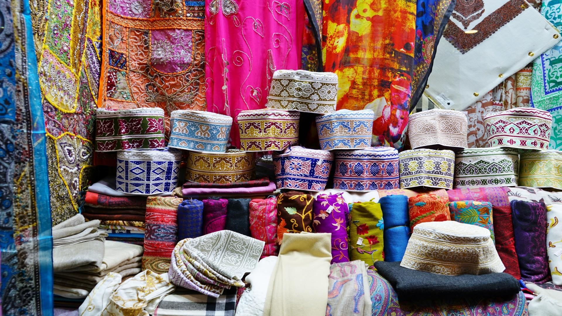 Mooie Kumma (Omani hoedjes) en andere kleding en stoffen, Muttrah souk, Muscat, Oman