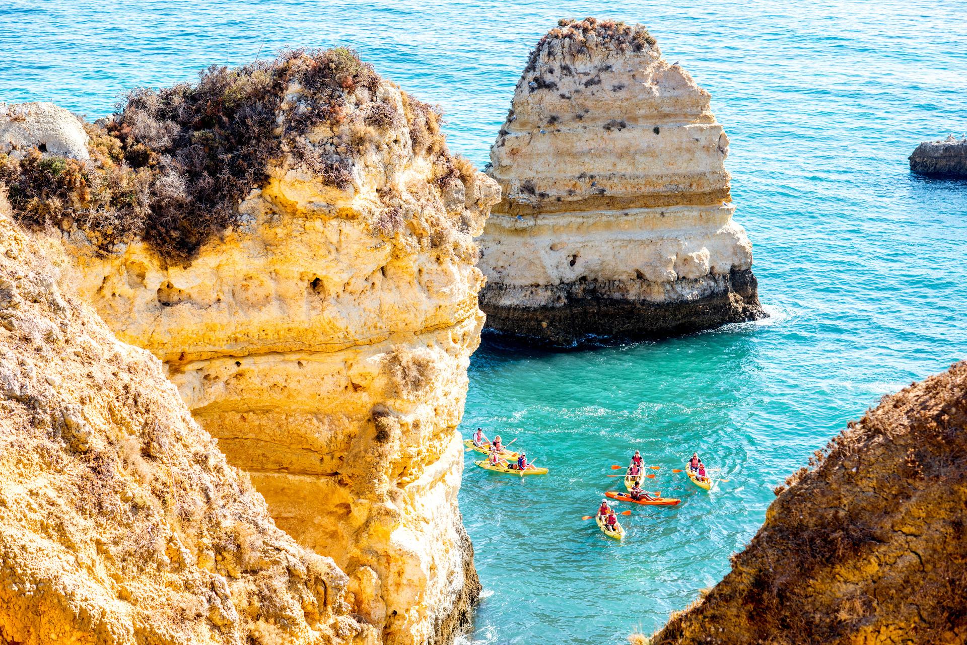 Rotsachtige kustlijn bij Ponta da Piedade met mensen kajaks, vlakbij de stad Lagos, Algarve, Portugal