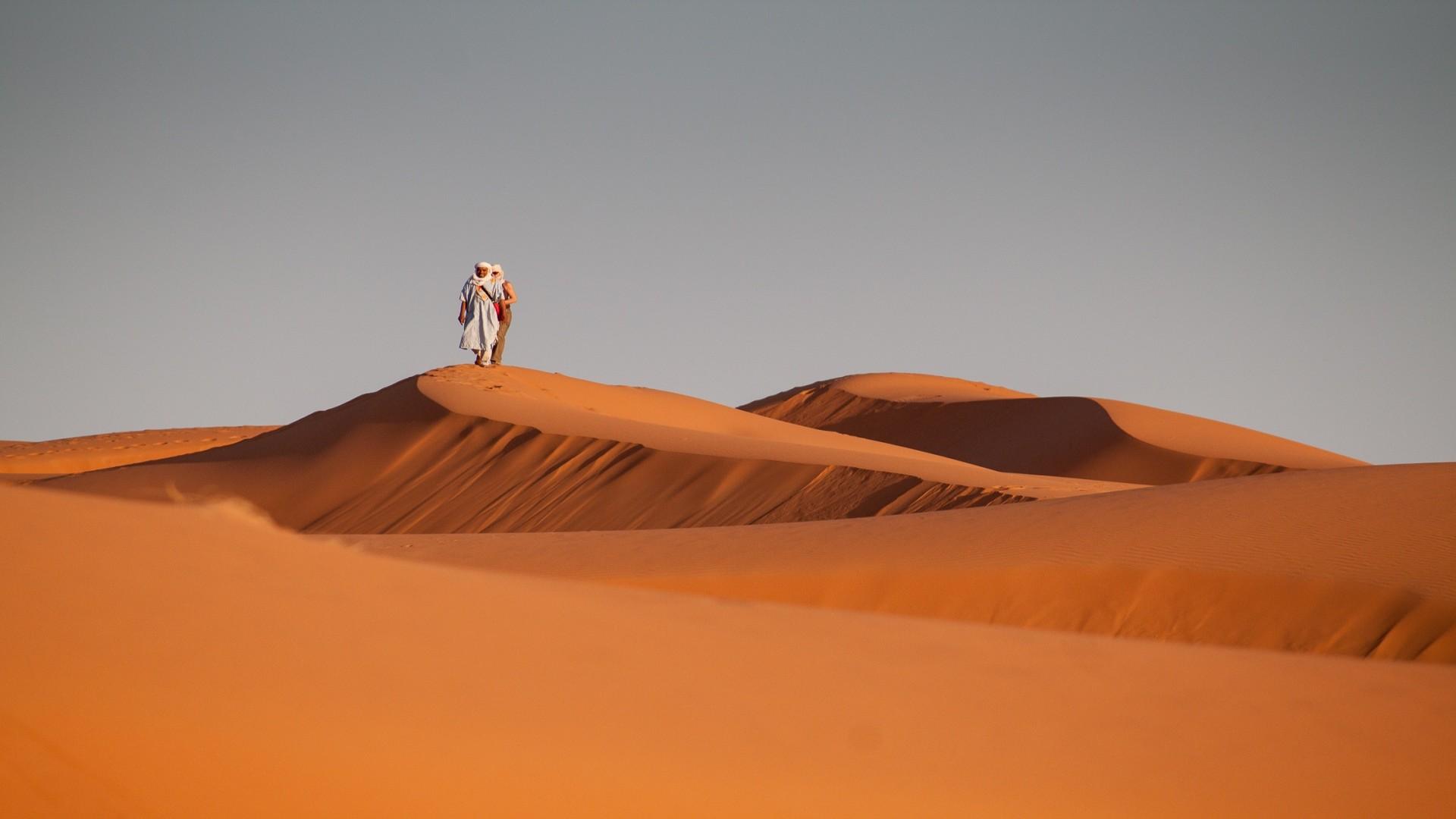 Man lopend in woestijn op oranje zandduin, Zuid Marokko