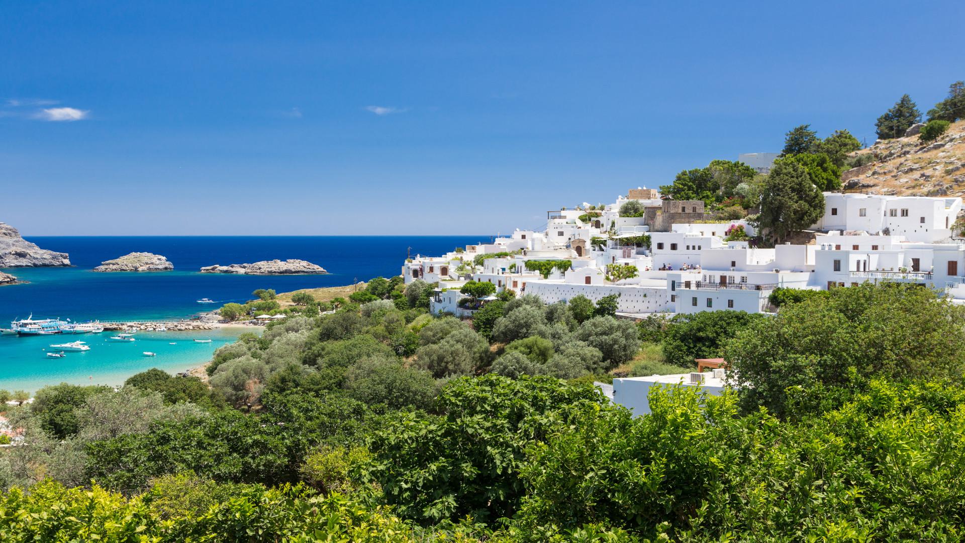Lindos, Rhodos, Griekenland, heuvel met witte huisjes en groene bomen