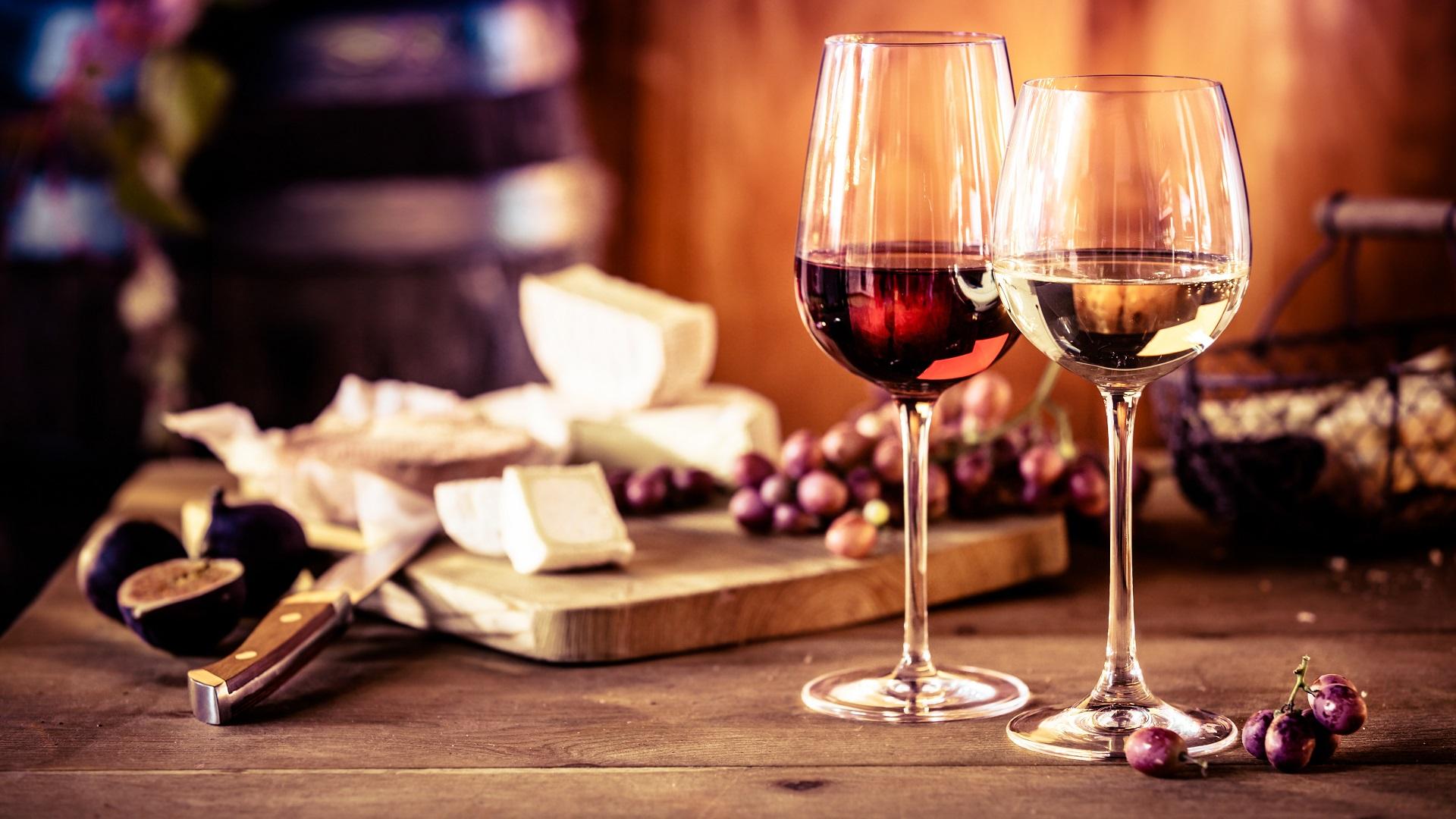 Kaasschotel met verse druiven en glazen rode en witte wijn op een rustieke houten tafel voor een brandend vuur in een taverne of wijnmakerij
