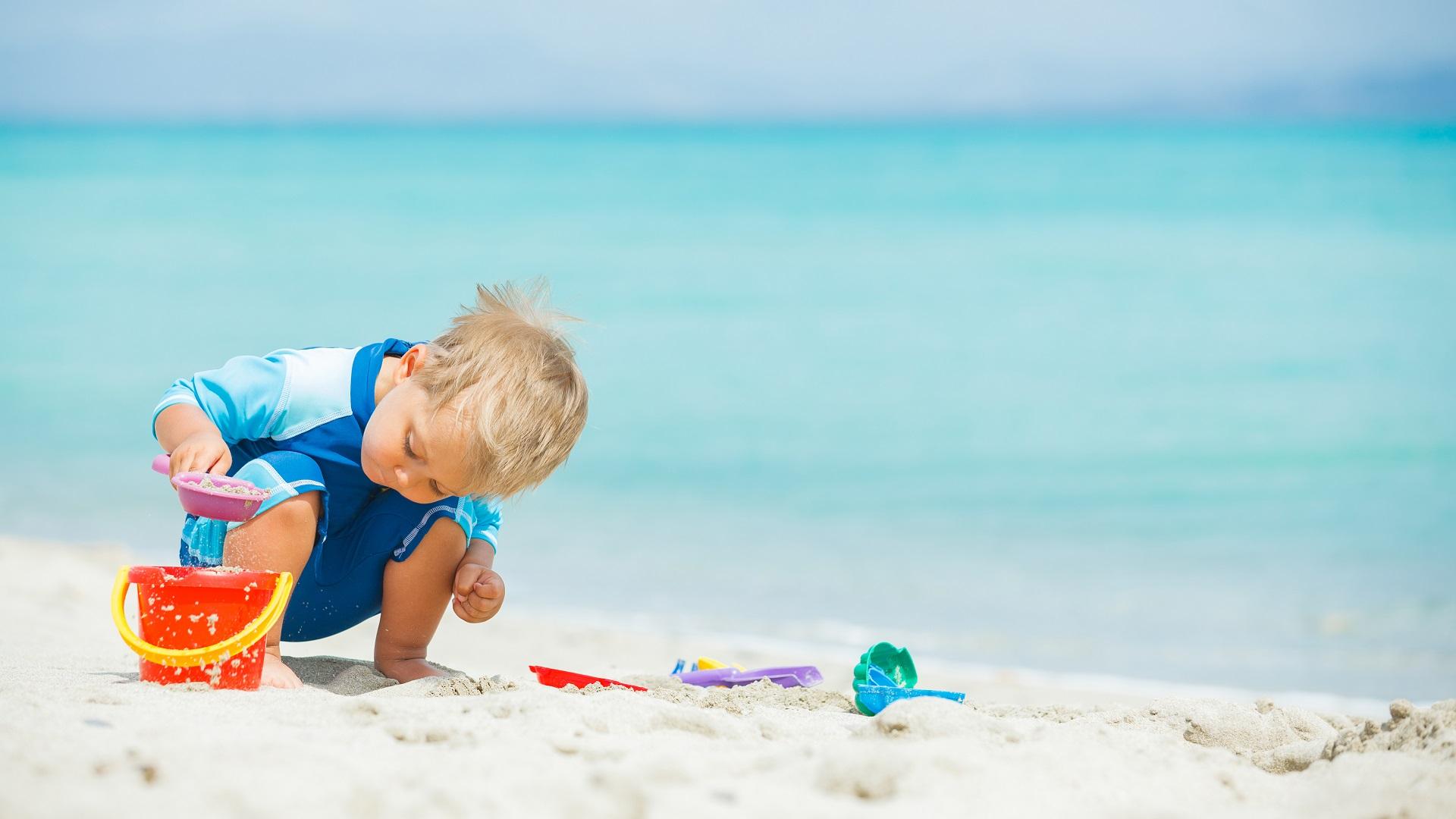 jongetje speelt op het strand