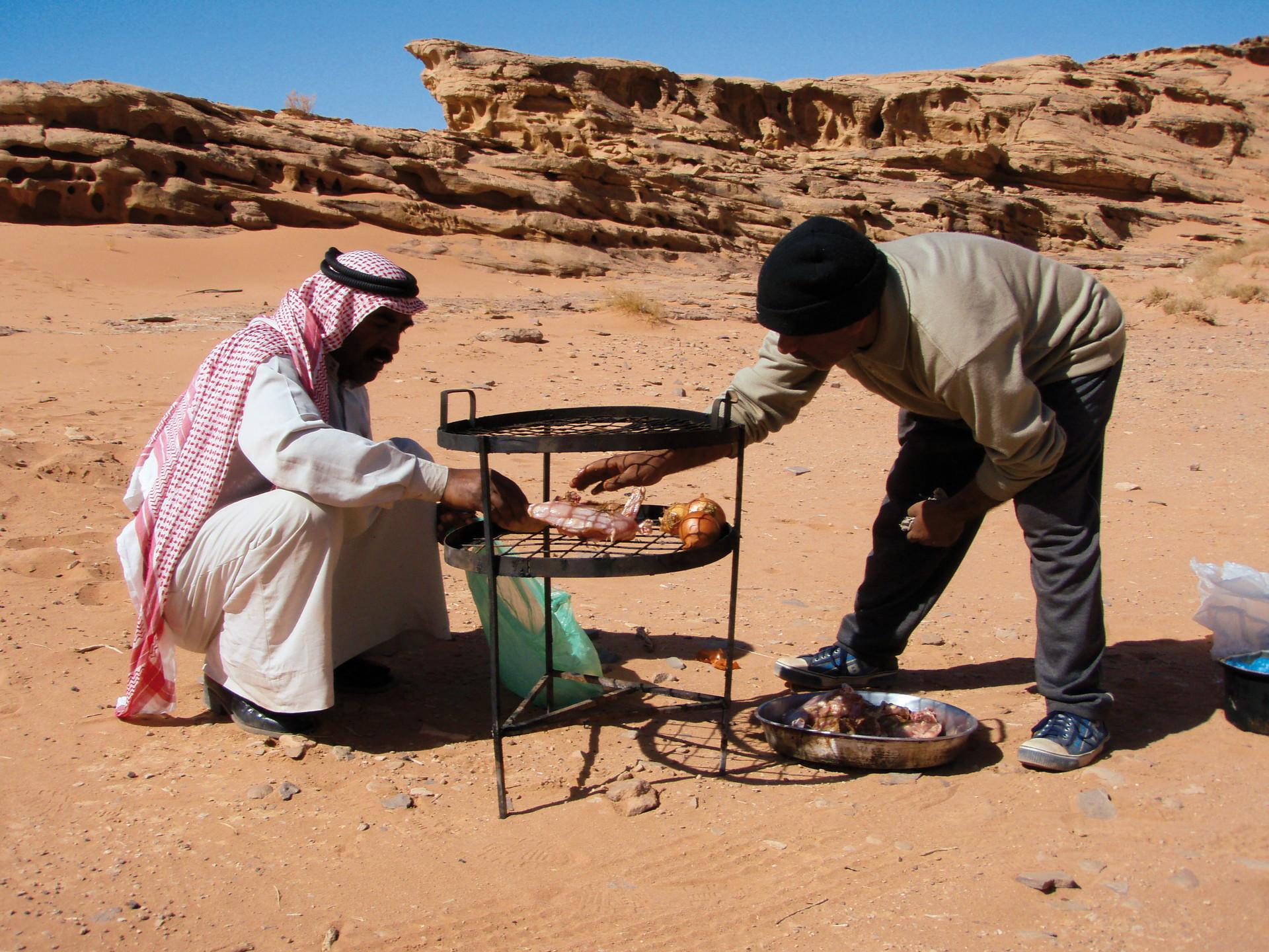Twee mannen bereiden Zharb voor, een ondergrondse barbecue, Wadi Rum, Jordanië