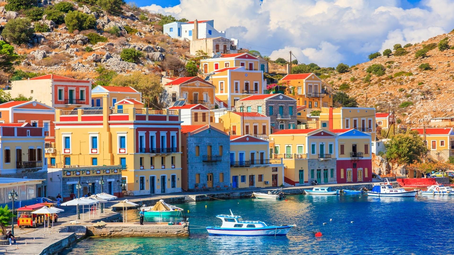 De haven van Symi, Griekenland, gekleurde huisje tegen een heuvel, water en bootjes