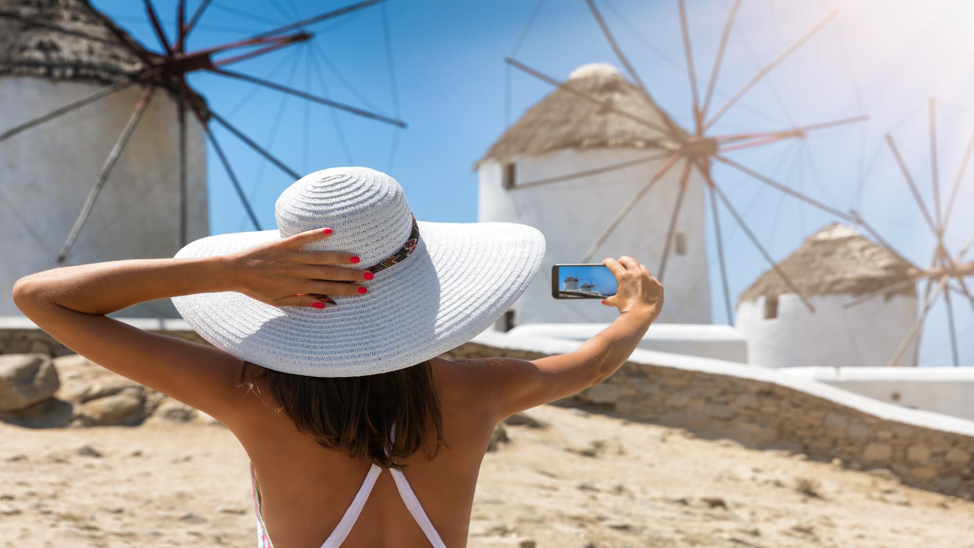 Vrouw met witte hoed, selfie bij molentjes Mykonos, Griekenland
