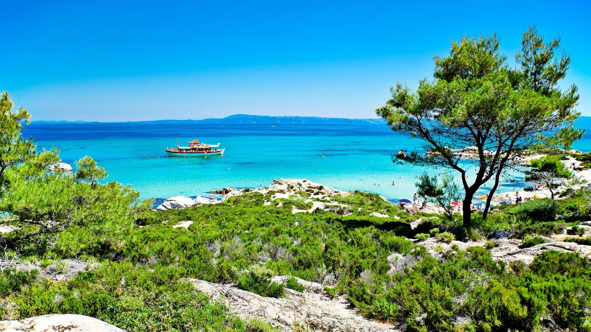 Een panorama van Portokali (Orange) Beach in Sithonia, Halkidiki, Griekenland met een toeristische schip. De oorspronkelijke naam is Kavourotripes
