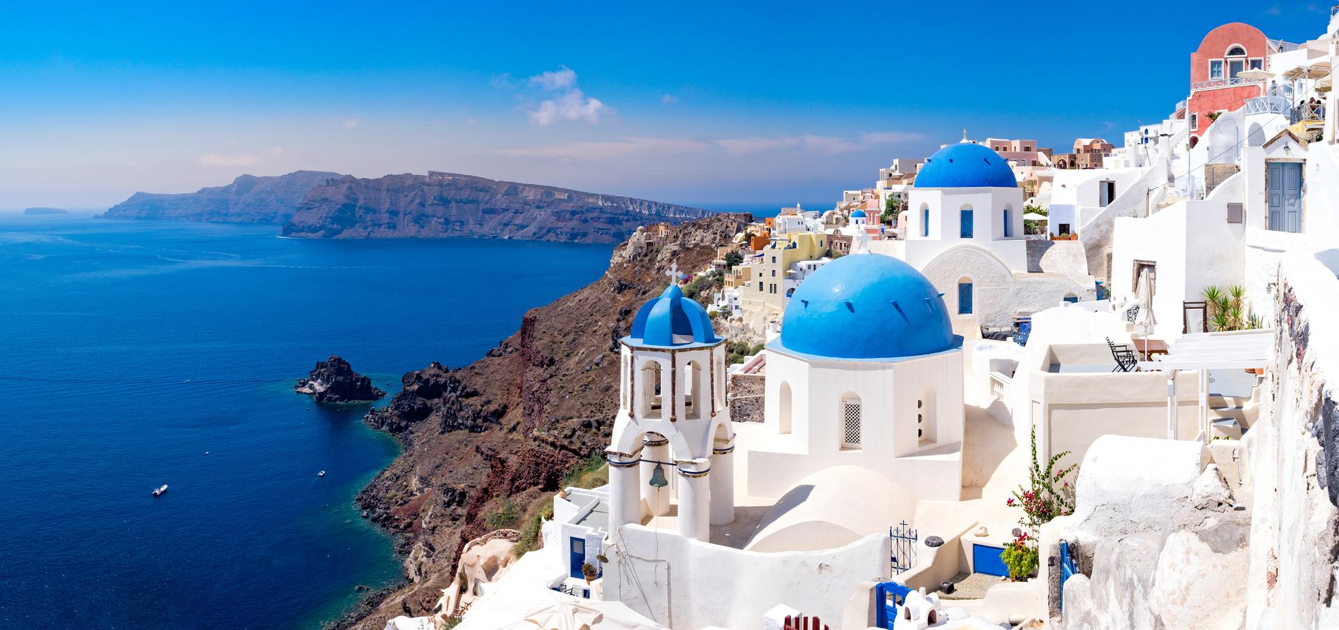 Panoramisch uitzicht op mooie witte huizen en blauwe koepels in Oia, Santorini, Griekenland