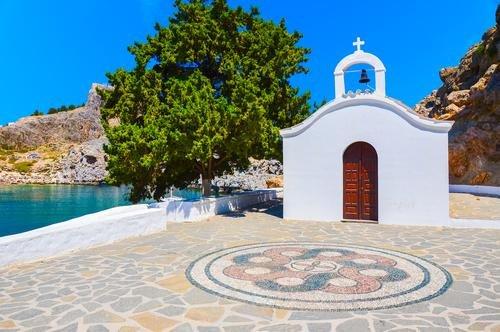 Een klein wit kerkje met een groene boom aan zee