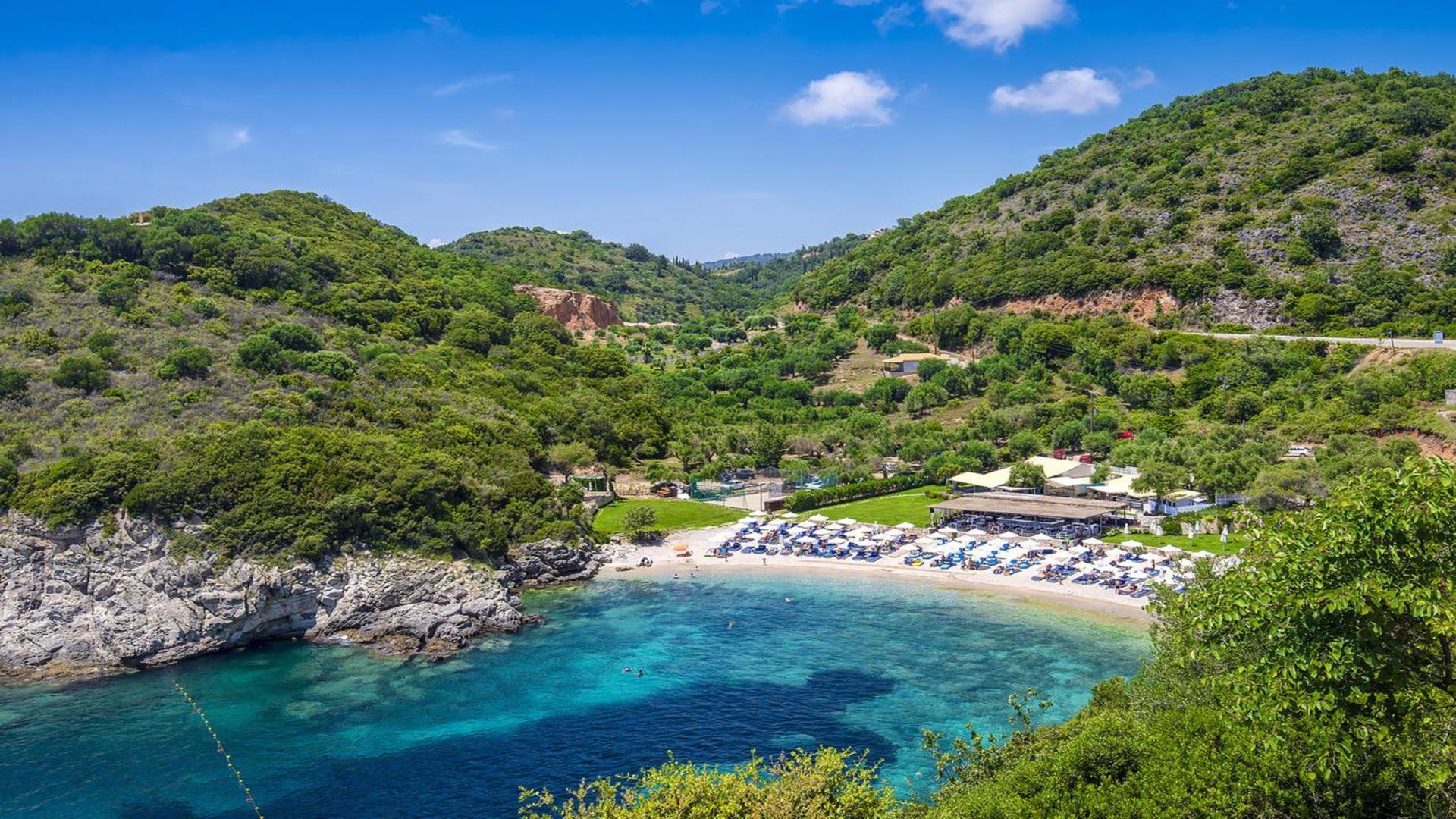 Strand omringd door blauw water en groene bomen op de heuvels, Albatros, Epirus, Griekenland
