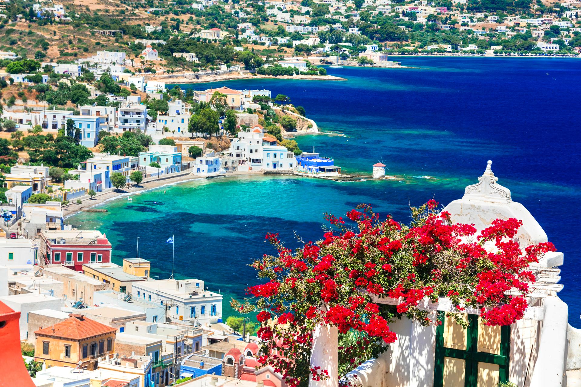 Leros - Agia Marina - blauw water, heuvels met groene bomen en witte huisjes, rode bloemen op de voorgrond