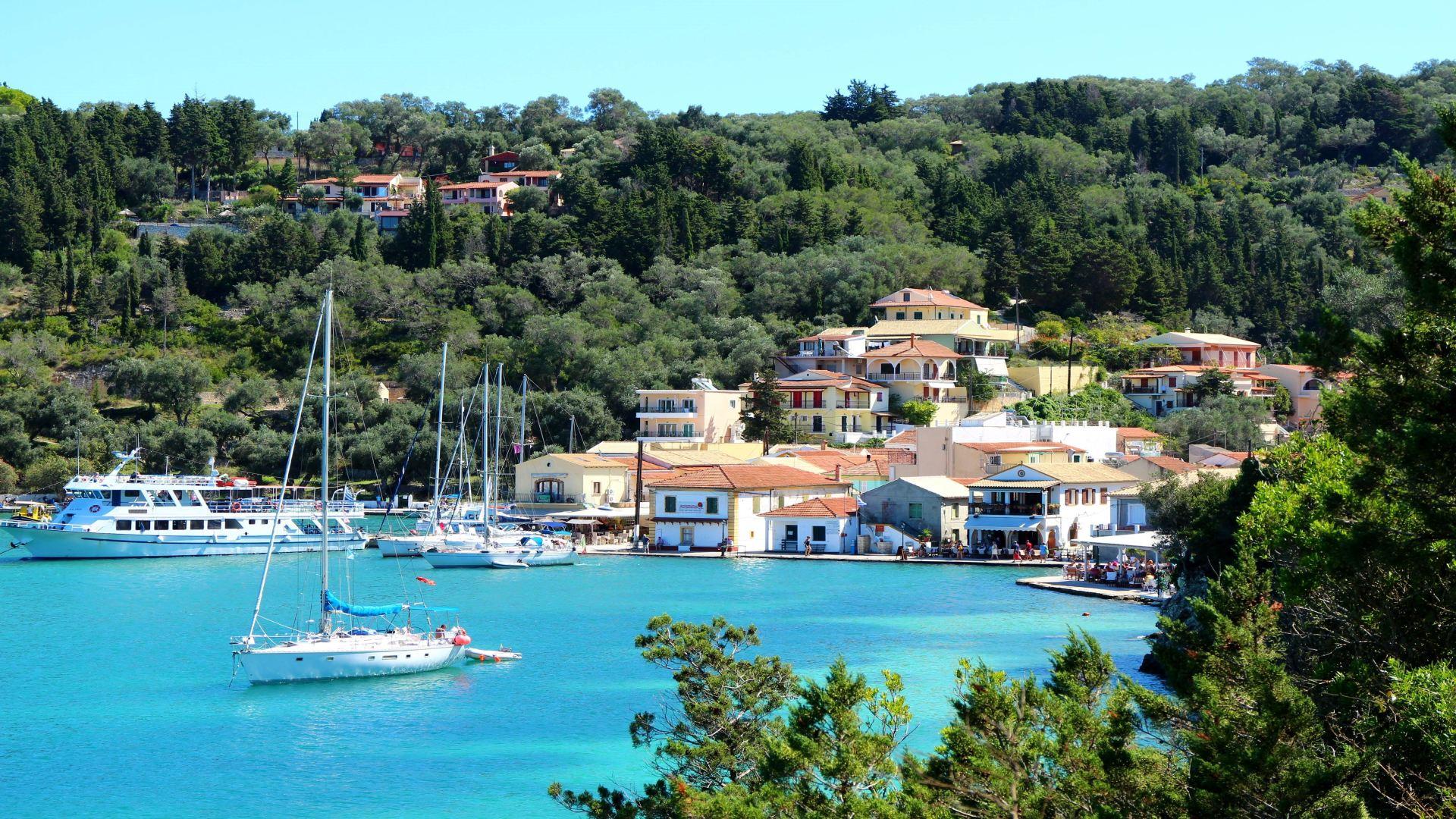 Lakka, Paxos, Griekenland, blauw water met bootjes, huisjes en groene bomen op heuvel