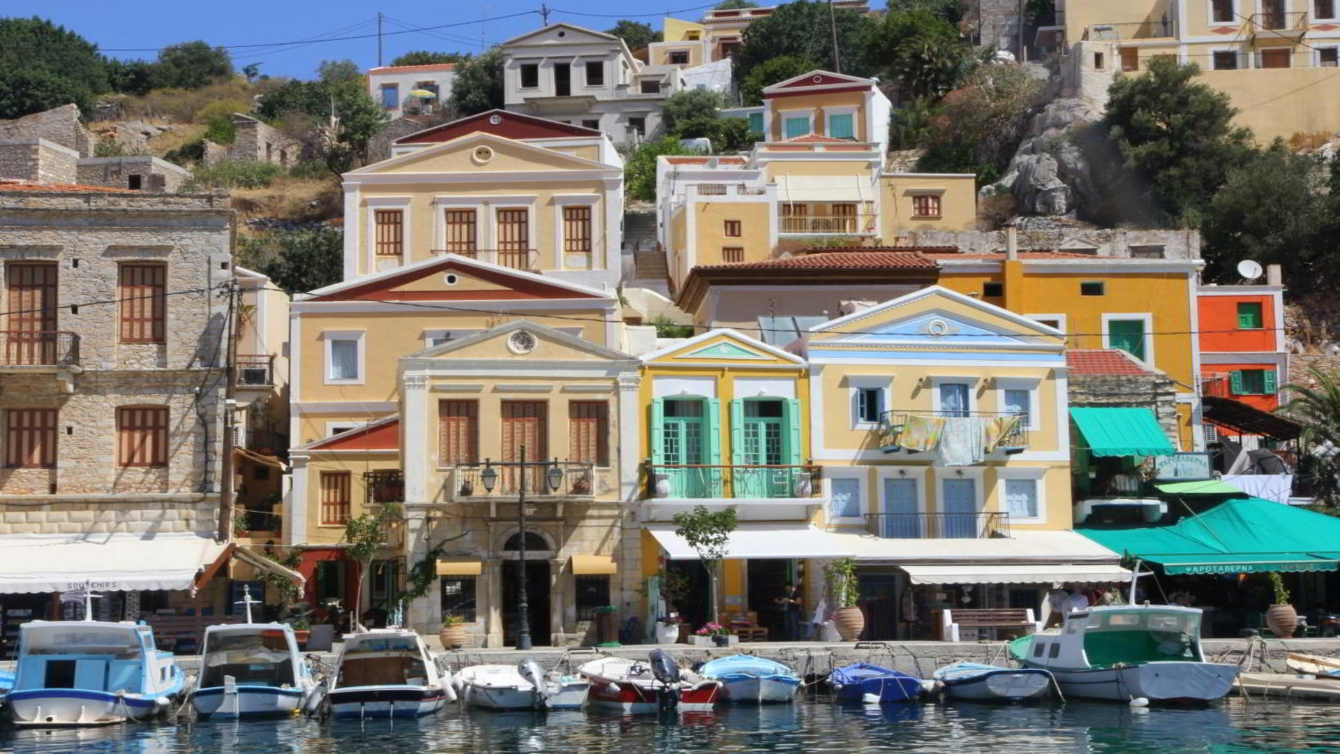 Gekleurde gebouwen en haven in Ano Symi, Symi Stad, Griekenland