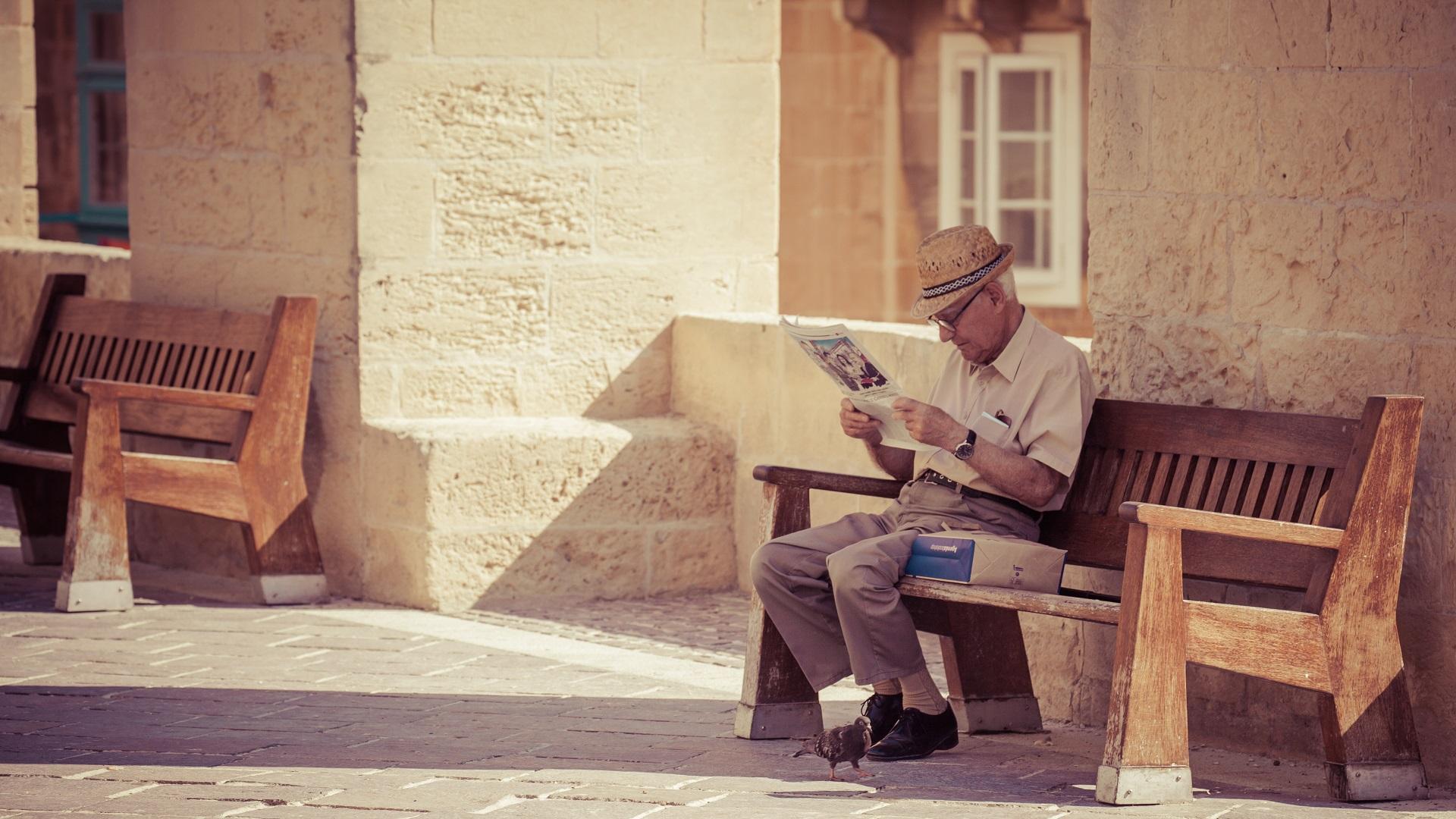 Oude man leest de krant op straat in Valletta