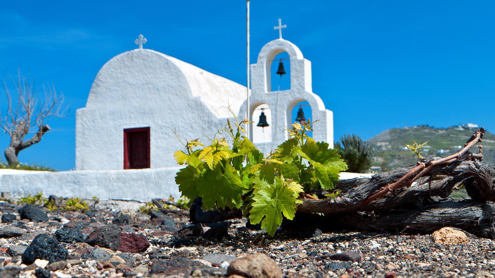 Het zwarte kiezelstrand voor een wit kerkje op Santorini