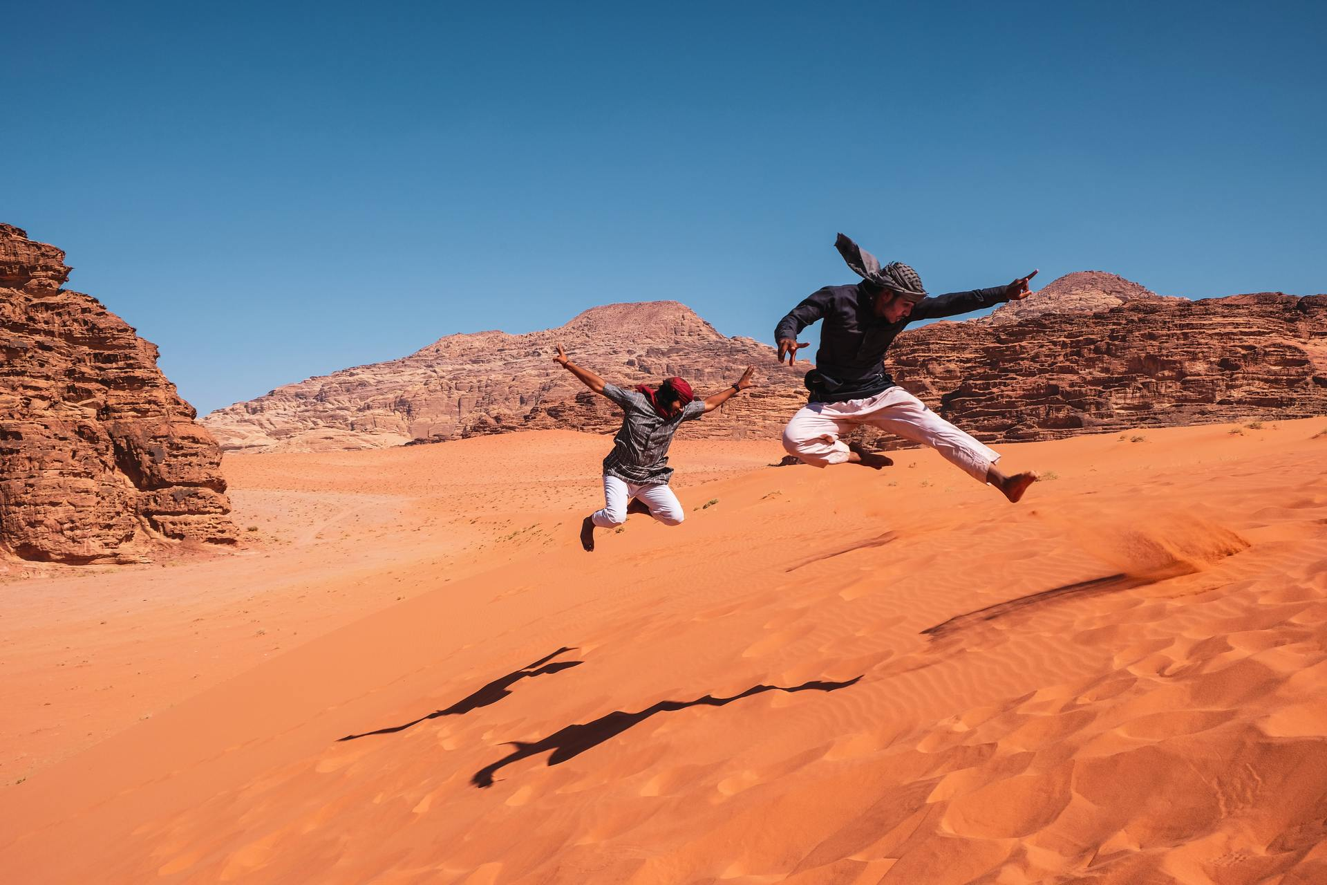 Springen op zandduin, Wadi Rum, Jordanië