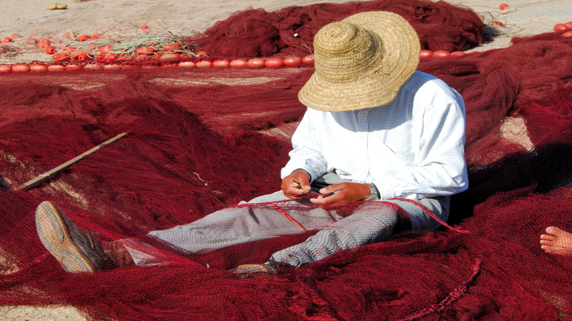 Visser met hoed repareert rode visnetten, Essaouira, Marokko