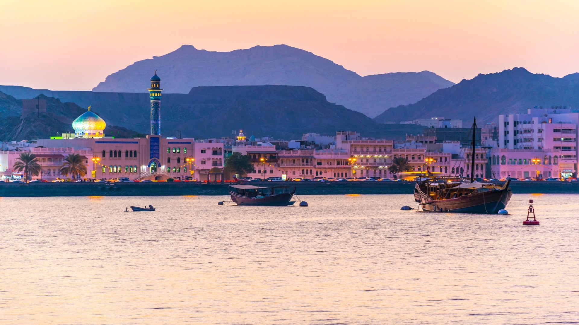 Uitzicht op de kustlijn van de wijk Muttrah in Muscat tijdens zonsondergang, Muscat, Oman