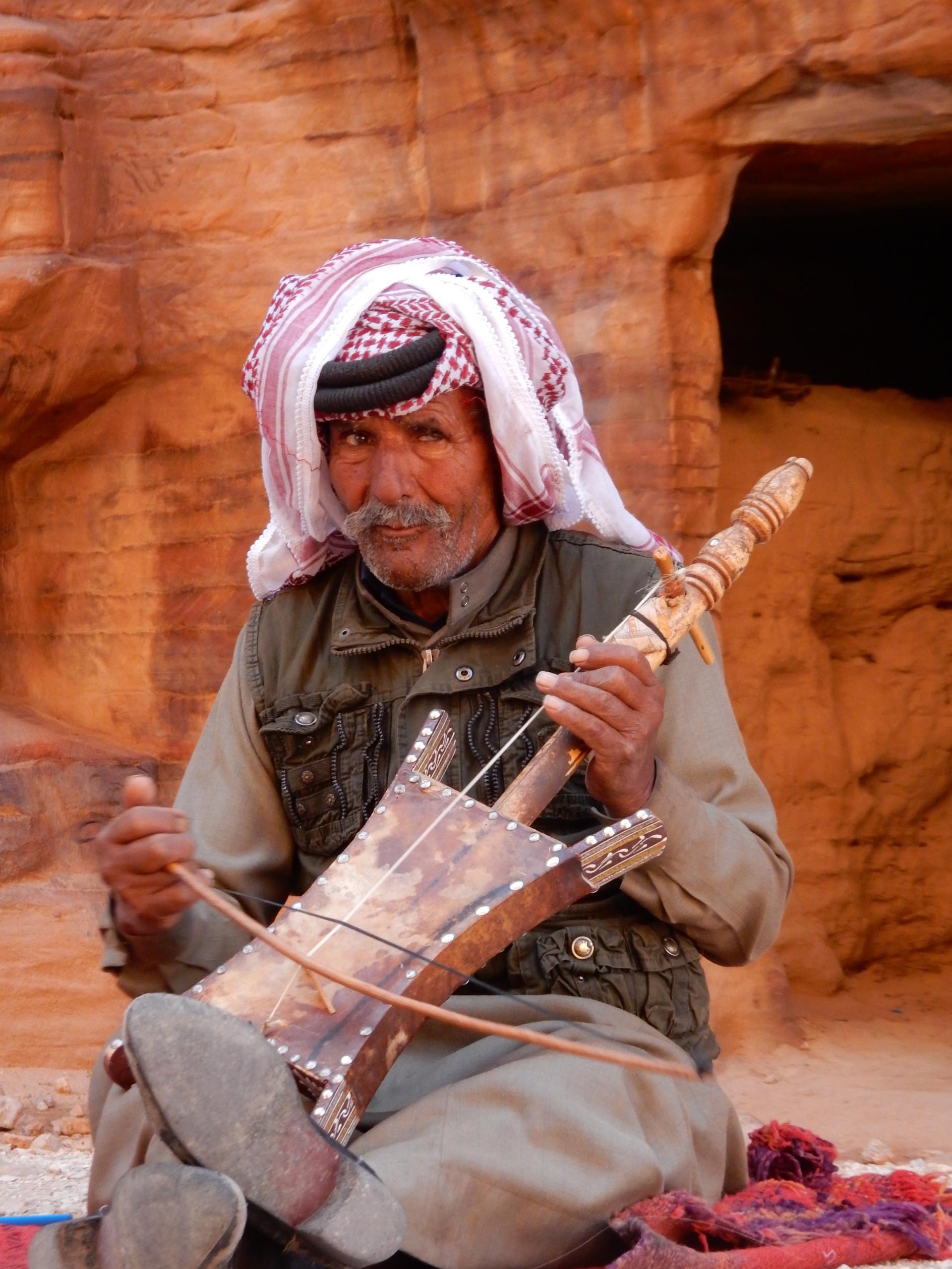 Man met muziekinstrument in Petra, Jordanië