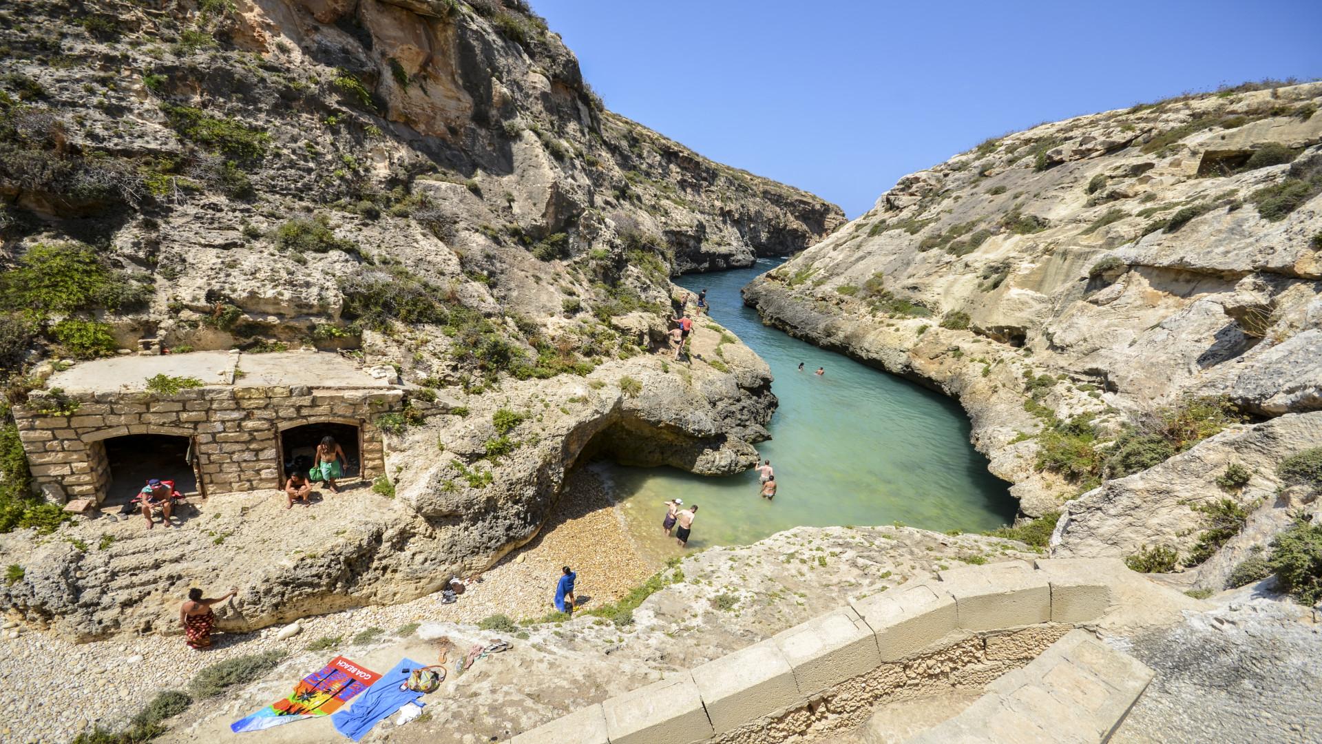 Klein strand tussen kliffen bij Wied il Ghasri, Gozo, Malta