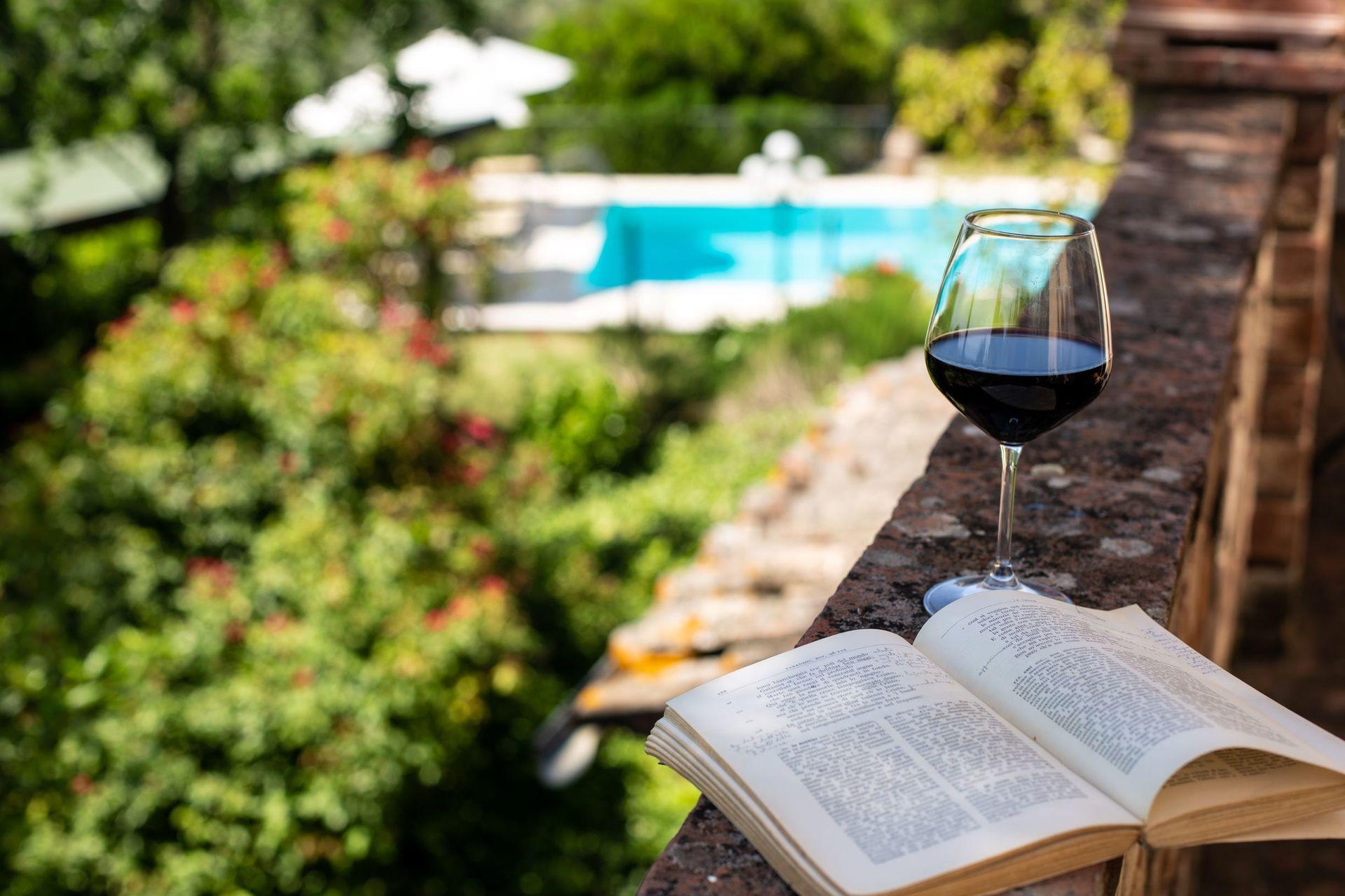 Glas wijn en boek Italie villa degli Olivi