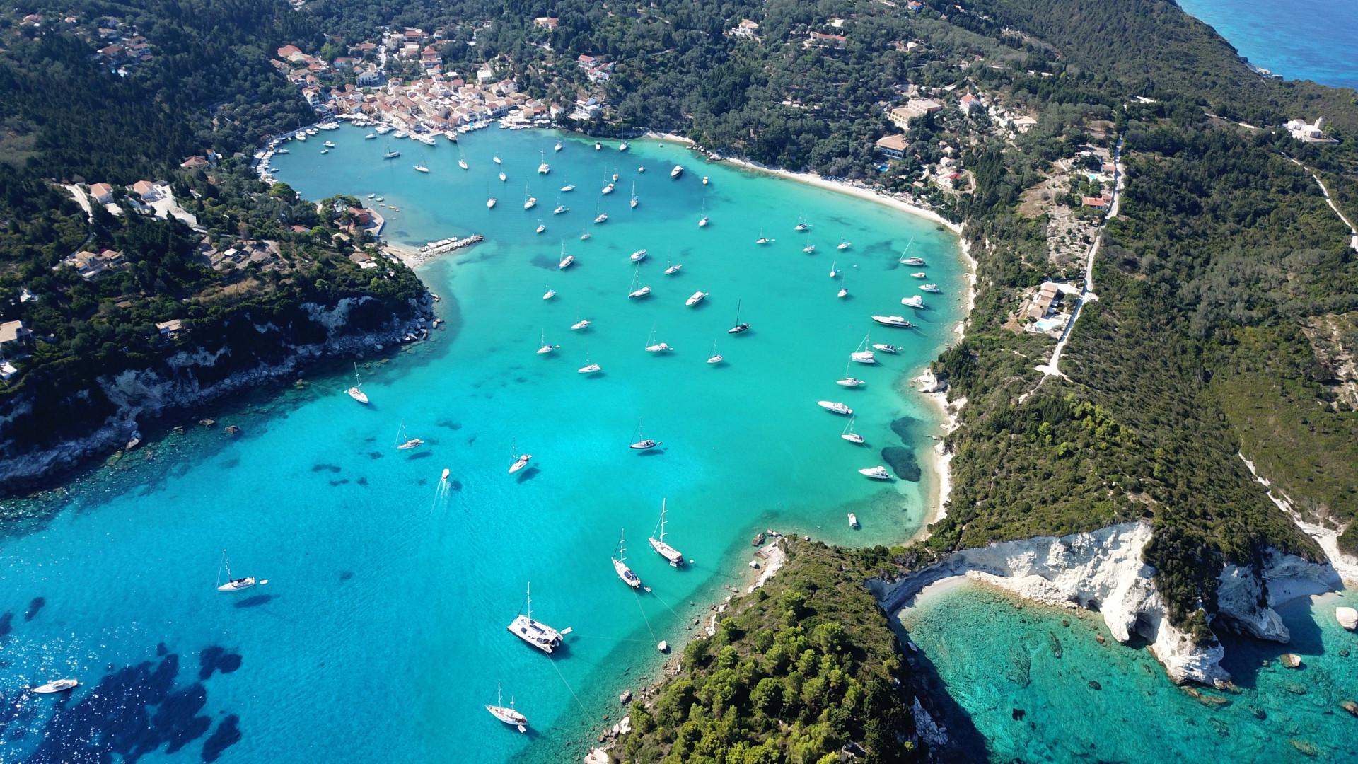 Luchtfoto van kleine haven en vissersdorpje Lakka met zeilboten in de baai, Paxos eiland, Griekenland