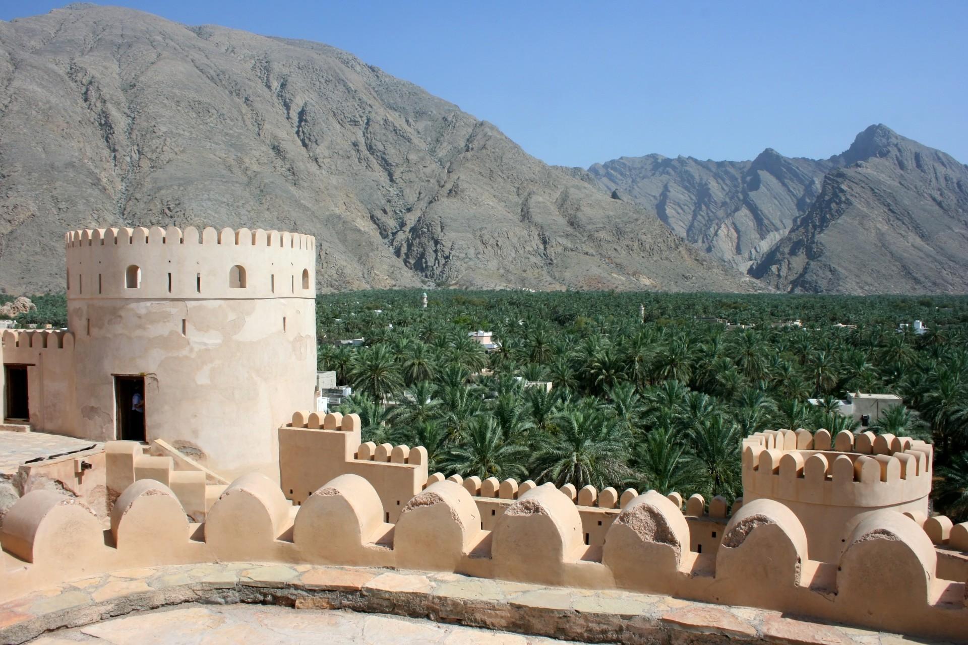 Fort Bahla met palmbomen en bergen op de achtergrond, Oman