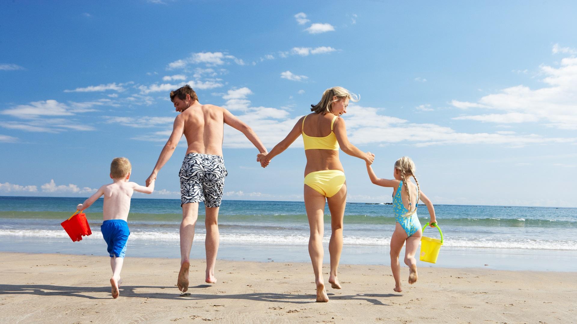 Ouders met kinderen op het strand