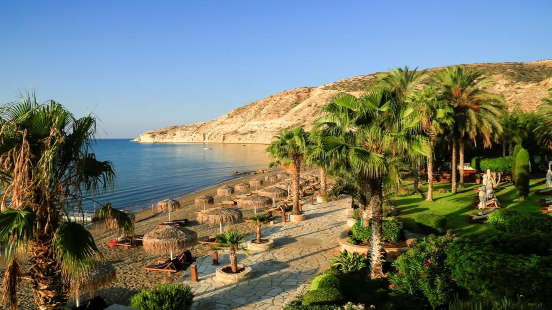Strand Pissouri met palmbonen, zee, heuvels, strandbedjes met parasol, Cyprus