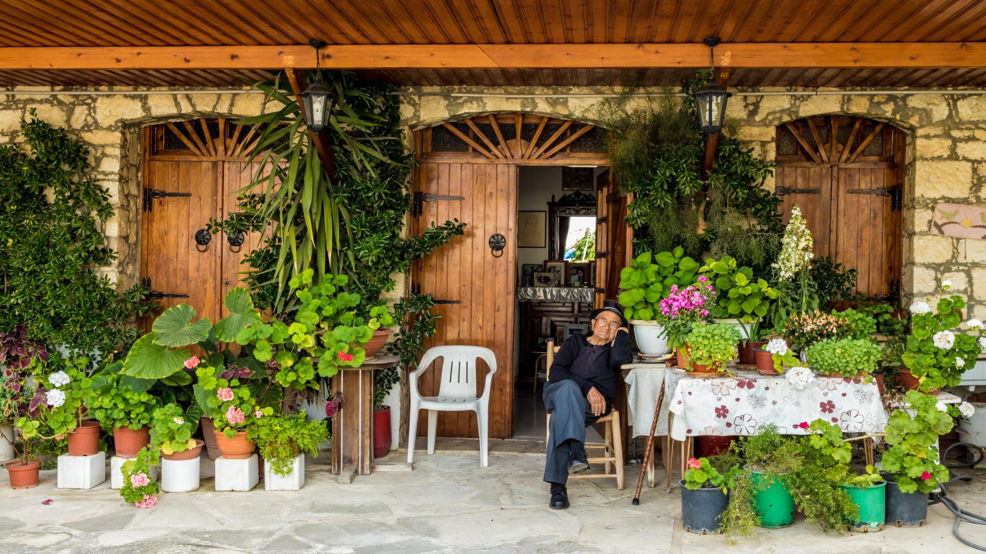 Een lokale man in zijn stoel in een prachtige tuin met planten in een dorpje in Omodos, Cyprus binnenland overig