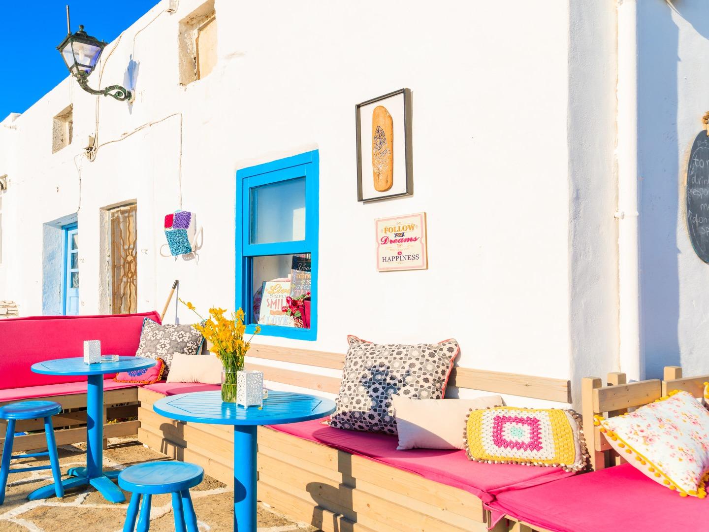 Naoussa terras, Paros, Griekenland, blauwe tafeltjes, rose kussens op de bank en wit gebouw