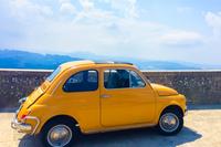 Auto Fiat 500 geel groot met uitzicht Italie