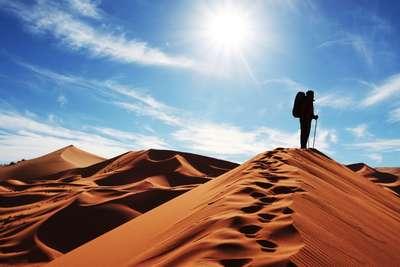 Man op duin in woestijn Marokko