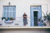 Griekenland oud vrouwtje op balkon blauwe luiken