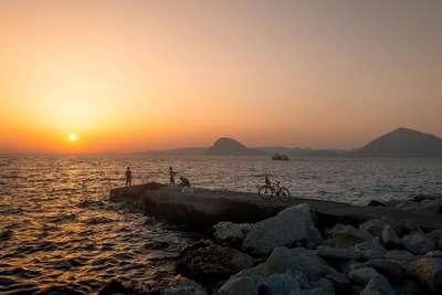 Zee, ondergaande zon en bergen op de achtergrond